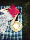 Woman reading a book and covering face outside Royalty Free Stock Photo