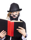 Woman reading book in disguise wearing black bowler hat fake beard and mustache with wide rimmed glasses Royalty Free Stock Images