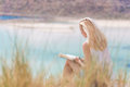 Woman reading book, enjoying sun on beach. Royalty Free Stock Photo