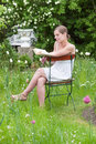 Woman reading a book in a garden young white summer dress sitting and Stock Photo