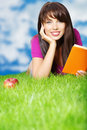 Woman reading book in the grass. sky background Royalty Free Stock Images