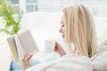Woman reading book while having coffee on sofa in living room Royalty Free Stock Image