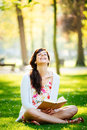 Woman reading book and having fun in park joyful sitting on grass Stock Photo