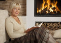 Woman reading book at home beautiful sitting next to a fireplace a looking camera Stock Photography