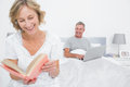 Woman reading book while husband is using laptop in bedroom at home Stock Images