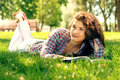 The woman reading a book lies on grass and Stock Photo