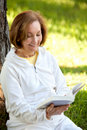 Woman reading a book outdoors Stock Photos
