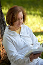 Woman reading a book outdoors Royalty Free Stock Image