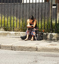 Woman reading book outdoors young reads a by sitting on the pavement in stoke newington london Stock Photos