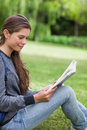 Woman reading a book while sitting on the grass Royalty Free Stock Images