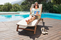 Woman reading book on sun lounger by pool beautiful young swimming Royalty Free Stock Images
