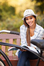 Woman reading book young sitting on bench in park smiling and looking into the camera Royalty Free Stock Photo