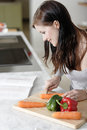 Woman reading cookery book beautiful young from a while cooking in her kitchen Royalty Free Stock Photo