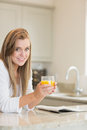 Woman reading while drinking orange juice in kitchen Royalty Free Stock Photos