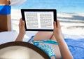 Woman reading e-book at beach Royalty Free Stock Photo