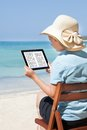 Woman Reading E-Book At Beach Royalty Free Stock Photo