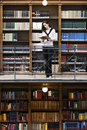 Woman reading in front of old bookshelf. Stock Photo