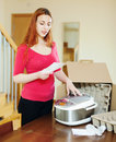 Woman reading guarantee card for new multicooker at home interior Stock Images