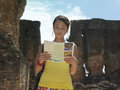 Woman reading guidebook with ancient ruins in background young mixed race the Royalty Free Stock Photo