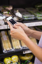 Woman reading her shopping list on smartphone close up view of a Royalty Free Stock Images