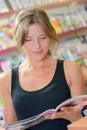 Woman reading magazine inside shop Royalty Free Stock Photo