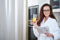 Woman reading the news while drinking orange juice in her kitchen Royalty Free Stock Photo