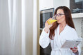 Woman reading the news while drinking orange juice in her kitchen Stock Photos