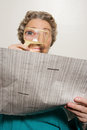 Woman reading newspaper with magnifying glass Royalty Free Stock Photo
