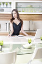Woman reading recipe book attractive young a while enjoying a glass of wine in the kitchen Royalty Free Stock Photography