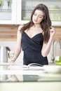 Woman reading recipe book attractive young a while enjoying a glass of wine in the kitchen Stock Images
