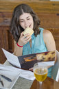 Woman reading restaurant menu anxiety card and eating bread Stock Images
