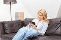 Woman reading on a tablet beautiful blond is sitting couch Royalty Free Stock Photo