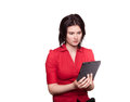 Woman reading a tablet in suspense studio shot of young holding pc with suspenseful expression Stock Images