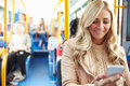 Woman reading text message on bus sitting chair smiling with passengers in background Stock Photography