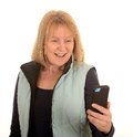 Woman reading text message smiling middle aged on a mobile telephone with a white studio background Royalty Free Stock Photo