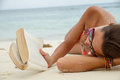 Woman reads a book on beach Stock Image