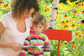 Woman reads book to little girl in garden Stock Images