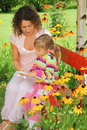 Woman reads book to little girl in garden Stock Photo
