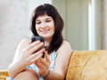 Woman reads sms in mobile at home Stock Image