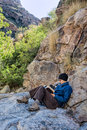 Woman reads on wilderness hike bald in black cap blue jacket and brown pants sits a rock and a book to rest while hiking in the Royalty Free Stock Images