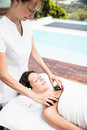 Woman receiving a hot stone massage from masseur in spa Stock Photography