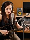 Woman in a recording studio photo of beautiful brunette playing an acoustic guitar and singing into large diaphragm microphone Royalty Free Stock Images