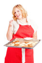 Woman with red apron blond present christmas cookies on a baking tray Royalty Free Stock Image