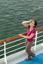Woman in red blouse travel on ship looks at sky Stock Image