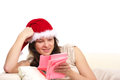 Woman in red christmas hat reading Royalty Free Stock Photo