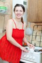Woman in red cleans gas stove with melamine sponge happy young kitchen at home Royalty Free Stock Photo