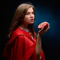 Woman with red cloak holding pomegranate beautiful in studio Stock Image