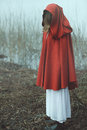 Woman with red cloak in misty desolated land sadness conceptual Stock Image