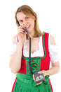 Woman in red dirndl dialing friend a Stock Photos