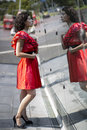 Woman in red dress adjust herself before mirror Royalty Free Stock Photos